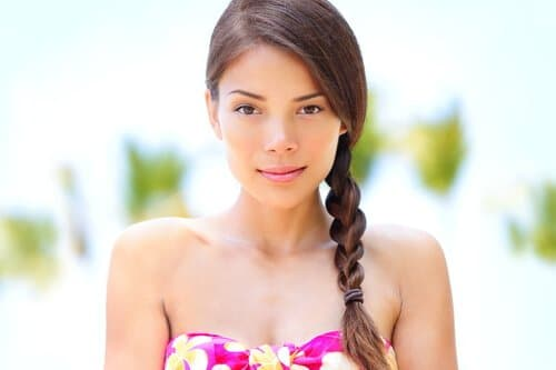 Wellness beauty tanned woman - portrait of relaxing spa serene mixed race asian caucasian model with dark braid looking smiling at camera. Beach on Hawaii