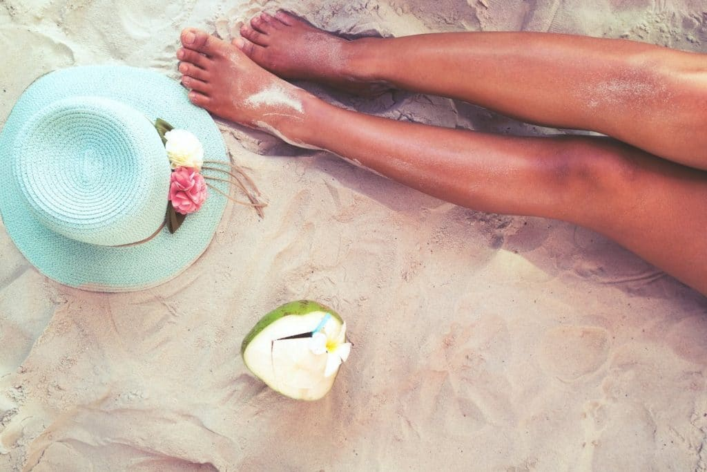 Legs in the sand with coconut maui soap co body mist hydrating body care